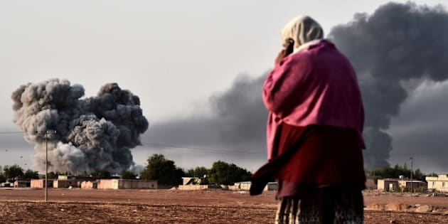 A woman watches as smoke rises after a strike from the US-led coalition on the the Syrian town of Ain al-Arab, known as Kobane by the Kurds, as seen from the Turkish-Syrian border in the southeastern village of Mursitpinar, Sanliurfa province, on October 13, 2014. The US-led international coalition carried out at least two new air strikes against positions held by Islamic State militants (IS) in and around Kobane on October 13, as meanwhile fighting broke out between Islamist jihadists and Kurdish fighters close to the Turkish border just north of the besieged Syrian town of Kobane. AFP PHOTO / ARIS MESSINIS        (Photo credit should read ARIS MESSINIS/AFP/Getty Images)