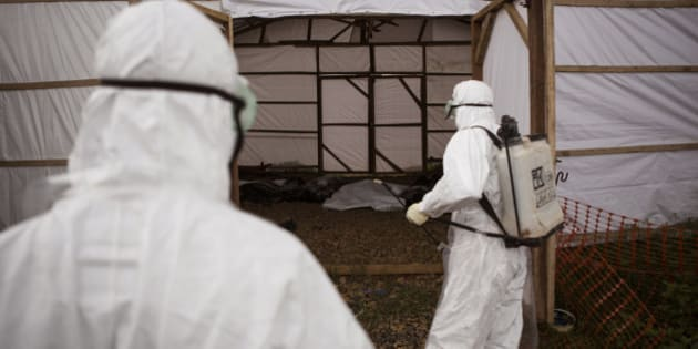 """In this photo taken on Wednesday, Sept. 24, 2014, healthcare workers spray disinfectant as they enter a makeshift morgue with the bodies of people suspecting of dying from the Ebola virus, in Kenema, Sierra Leone, Thursday, Sept. 25, 2014.  Sierra Leone restricted travel Thursday, Sept. 25, 2014 in three more """"hotspots"""" of Ebola where more than 1 million people live, meaning about a third of the country's population is now under quarantine. Sierra Leone is one of the hardest hit countries in the Ebola outbreak sweeping West Africa that is believed to have killed more than 2,900 people, according to World Health Organization tolls published Thursday. (AP Photo/ Tanya Bindra)"""