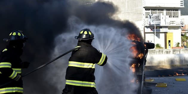 Firefighters try to put out a blazing car after students set the Municipal Palace on fire in Chilpancingo, Guerrero state during a protest to demand the finding of the 43 peers missing since an attack by rogue officers earlier this month. Authorities are investigating whether the students were buried in mass graves found outside Iguala, a city 200 kilometers (125 miles) south of Mexico City.  AFP PHOTO/ Yuri CORTEZ        (Photo credit should read YURI CORTEZ/AFP/Getty Images)