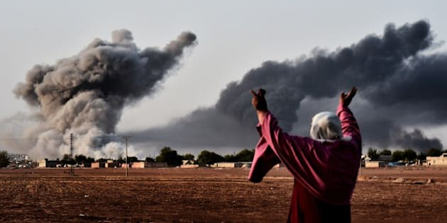 A woman reacts as smoke rises from the the Syrian town of Ain al-Arab, known as Kobane by the Kurds, after a strike from the US-led coalition as it seen from the Turkish - Syrian border in the southeastern village of Mursitpinar, Sanliurfa province, on October 13, 2014. AFP PHOTO / ARIS MESSINIS        (Photo credit should read ARIS MESSINIS/AFP/Getty Images)