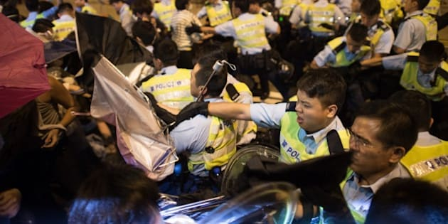 Police and pro-democracy protesters scuffle during a confrontation outside the central government offices in the Admiralty district of Hong Kong on October 15, 2014. Hong Kong police vowed October 14 to tear down more street barricades manned by pro-democracy protesters, hours after hundreds of officers armed with chainsaws and boltcutters partially cleared two major roads occupied for a fortnight. AFP PHOTO / Ed Jones        (Photo credit should read ED JONES/AFP/Getty Images)