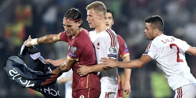 Serbia's  Nemanja Gudelj (L) scuffles with midfielder Albania's midfielder Bekim Balaj (C) and defender  Andi Lila (R) over a flag with Albanian national symbols pulled down from a remotely operated drone flown over the pitch  during the EURO 2016 group I football match between Serbia and Albania in Belgrade on October 14, 2014.  AFP PHOTO / ANDREJ ISAKOVIC        (Photo credit should read ANDREJ ISAKOVIC/AFP/Getty Images)