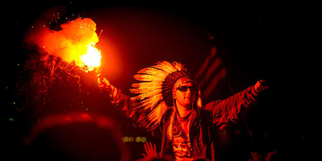 GLASTONBURY, UNITED KINGDOM - JULY 08: A man in the crowd wearing a Native American Headdress holding a lit flare as Jake Bug performs headlining The Other stage at the end of Day 2 of The Glastonbury Festival  at Worthy Farm on July 8, 2014 in Glastonbury, England. (Photo by Ollie Millington/Redferns via Getty Images)