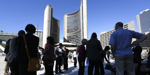 TORONTO, ON - SEPTEMBER 25:   City Hall workers gather in Nathan Phillips Square after the evacuation. A fire broke out in a hydro vault under the north-west corner of City Hall Thursday afternoon.  Fire officials claim the fire was starting during some maintenance work.  Several people were treated for very mild smoke inhalation.  City Hall was evacuated and the building was left without power.        (Richard Lautens/Toronto Star via Getty Images)