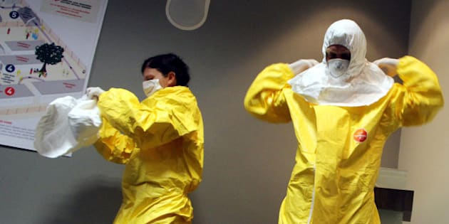 JOHANNESBURG, SOUTH AFRICA - OCTOBER 14: Dr Stefan Kruger and Dr. Juli Switala who have worked with Medecins Sans Frontieres (MSF) show how to put on special uniform to prevent from Ebola virus after they hold press conference in Johannesburg, South Africa, on October 14, 2014. (Photo by Hassan Isilow/Anadolu Agency/Getty Images)