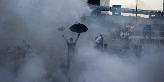 TOPSHOTS A pro-democracy demonstrator gestures after police fired tear gas towards protesters near the Hong Kong government headquarters on September 28, 2014. Police fired tear gas as tens of thousands of pro-democracy demonstrators brought parts of central Hong Kong to a standstill on September 28, in a dramatic escalation of protests that have gripped the semi-autonomous Chinese city for days. AFP PHOTO / XAUME OLLEROS        (Photo credit should read XAUME OLLEROS/AFP/Getty Images)