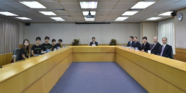 CORRECTS NAMES OF HONG KONG STUDENT LEADERS  Leaders of the Hong Kong Federation of Students (L-R) Yvonne Leung, Nathan Law, Alex Chow, Lester Shum and Eason Chung, and Hong Kong government representatives (5th R-R) Edward Yau, Rimsky Yuen, Carrie Lam, Raymond Tam and Lau Kong and mediator, Leonard Cheng Kwok-hon (C), chairman of Lingnan University, look on before commencing their long-awaited talks to formally discuss demands raised by student protesters in Hong Kong on October 21, 2014. Hong Kong's leader Leung Chun-ying has said open elections would result in the city's many poor dominating politics, as he ruled out democratic reforms before crucial talks aimed at ending three weeks of protest rallies.   AFP PHOTO / Philippe Lopez        (Photo credit should read PHILIPPE LOPEZ/AFP/Getty Images)