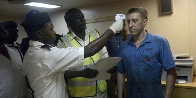 Health officials takes the body temperature of an Ukrainian sailor on the MV Pintail ship, as they check for signs of the Ebola virus at the Apapa Sea Port, in Lagos, on September 29, 2014. Health officials have begun the screening of cargo ship crews transiting through the ports of Nigeria to prevent cross border transmission of Ebola through sea and cargo ports. Nigeria has cleared all patients under surveillance for the Ebola virus, the federal health ministry said on September 24, 2014. 'There is nobody again under surveillance for the Ebola virus in any part of Nigeria. All those under surveillance have completed their mandatory 21-day period stipulated by the WHO,' ministry's spokesman Dan Nwomeh told AFP, referring to the World Health Organization.  PHOTO/PIUS UTOMI EKPEI        (Photo credit should read PIUS UTOMI EKPEI/AFP/Getty Images)