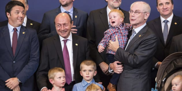 European Council President Herman Van Rompuy, second right, holds his grandson as he poses with EU heads of state during a group photo at an EU summit in Brussels, on Thursday, Oct. 23, 2014. EU leaders gathered Thursday for a two-day summit in which they will discuss Ebola, climate change and the economy. President Van Rompuy is attending his last EU summit as EU Council president and brought his family along to the group photo. Other leaders from left, Italian Prime Minister Matteo Renzi, Belgian Prime Minister Charles Michel, Romanian President Traian Basescu, Spanish Prime Minister Mariano Rajoy and Swedish Prime Minister Stefan Lofven. (AP Photo/Geert Vanden Wijngaert)