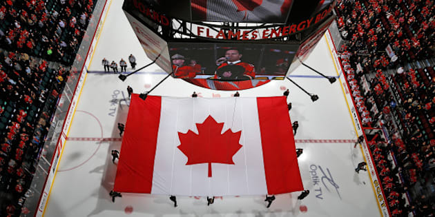 CALGARY, AB - OCTOBER 23: A giant Canadian flag is displayed in a moment of silence for the Ottawa shooting tragedy before the game between the Calgary Flames and the Carolina Hurricanes at Scotiabank Saddledome on October 23, 2014 in Calgary, Alberta, Canada. (Photo by Gerry Thomas/NHLI via Getty Images)