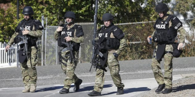 Law enforcement officers dressed in tactical gear leave the Gold County Fairgrounds to help in the search of an assailant, in Auburn, Calif.,  who shot three sheriff's deputies in two Northern California Counties, Friday, Oct. 24, 2014.  Deputies were searching a canyon in the Sierra Nevada foothills for an armed man suspected in the shooting of a Sacramento County Sheriff's deputy and two Placer County Deputies and a bystander in an attempt to carjack a vehicle.(AP Photo/Rich Pedroncelli)