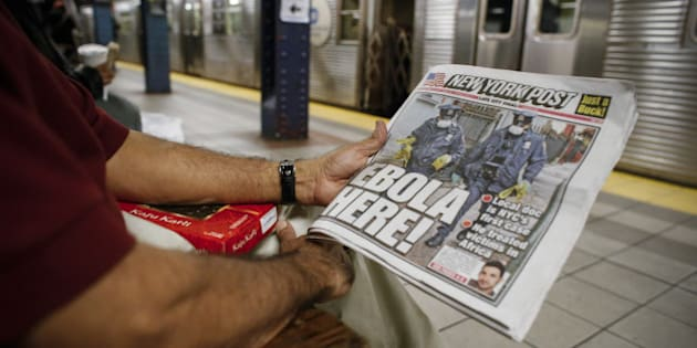 NEW YORK, NY - OCTOBER 24: A man shows the front page of a local newspaper while reading in the subway on October 24, 2014 in New York City. Dr. Craig Spencer, who returned to New York from Guinea 10 days ago, tested positive for Ebola on October 23 and is now being cared for at Bellevue Hospital. Spencer, a member of Doctors Without Borders, rode the subway after returning home. (Photo by Kena Betancur/Getty Images)