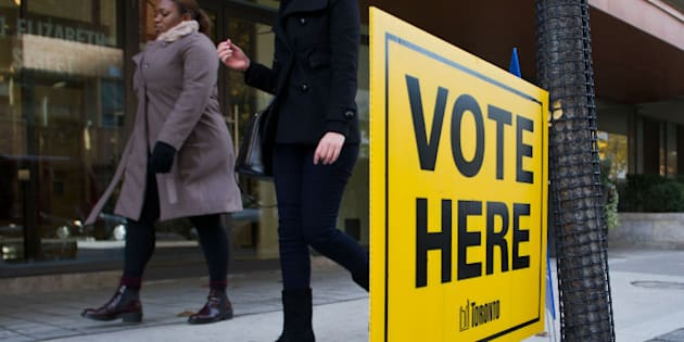 Women walk past a 'Vote Here' sign displayed outside of One City Hall in Toronto, Ontario, Canada, on Monday, Oct. 27, 2014. Toronto votes for a mayor today in an election that pits Doug Ford's subways against John Tory's surface rail in a race that has largely revolved around easing one of North America's longest commute times. Photographer: Galit Rodan/Bloomberg via Getty Images