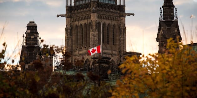 OTTAWA, ON - OCTOBER 23:  A flag next to the Canadian Parliament Building is flown at half-staff one day after Cpl. Nathan Cirillo of the Canadian Army Reserves was killed while standing guard in front of the National War Memorial by a lone gunman, on October 23, 2014 in Ottawa, Canada. After killing Cirillo the gunman stormed the main parliament building, terrorizing the public and politicians, before he was shot dead.  (Photo by Andrew Burton/Getty Images)