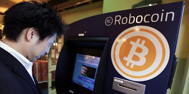 Customer Kiyono Yuichi purchases bitcoins from the BMEX bitcoin exchange's Robocoin-branded automated teller machine (ATM) at The Pink Cow restaurant and bar in Tokyo, Japan, on Wednesday, June 18, 2014. Bitcoin, proposed by an anonymous programmer or programmers in 2008, has drawn entrepreneurs and retailers looking to popularize it as a low-cost alternative to established payment systems, supplanting credit cards to international wire transfers. Photographer: Yuriko Nakao/Bloomberg via Getty Images