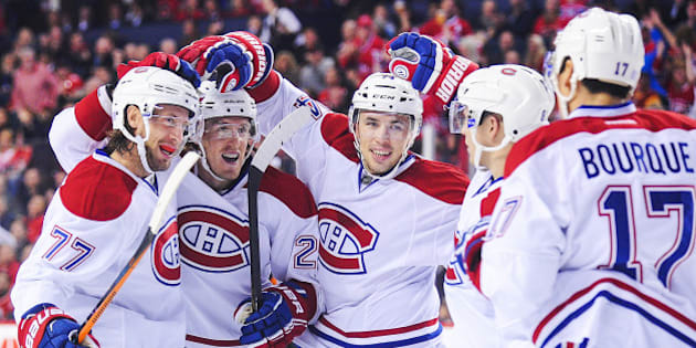 CALGARY, AB - OCTOBER 28: Tom Gilbert #77 (L) of the Montreal Canadiens celebrates with his teammates after scoring against the Calgary Flames during an NHL game at Scotiabank Saddledome on October 28, 2014 in Calgary, Alberta, Canada. (Photo by Derek Leung/Getty Images)