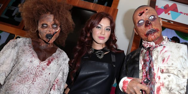 LOS ANGELES, CA - OCTOBER 31:  VEVO Singer Guinevere (C) poses with two 'zombies' at her live performance and meet & greet at VEVO headquarters on October 31, 2013 in Los Angeles, California.  (Photo by David Livingston/Getty Images)