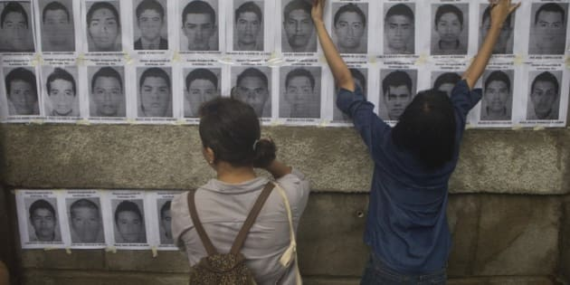Nicaraguan demonstrators post leaflets, in protest, with the images of disappeared Mexican rural college students on the outer walls of the Mexican embassy in Managua, Nicaragua, Wednesday, Oct. 22, 2014. The Mexican government says it still does not know what happened to the young people after they were rounded up by local police in Iguala, a town in southern Mexico, and allegedly handed over to gunmen from a drug cartel Sept. 26, even though authorities have arrested 50 people allegedly involved. They include police officers and alleged members of the Guerreros Unidos cartel. (AP Photo/Esteban Felix)