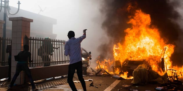 A car burns outside the parliament building in Burkina Faso as people protest  against their longtime President Blaise Compaore  who seeks another term in Ouagadougou, Burkina Faso, Thursday, Oct. 30, 2014. Protesters stormed Burkina Faso's parliament Thursday, dragging furniture and computers onto the street and setting the main chamber ablaze, in the most significant challenge to the president's rule during his 27 years in power.(AP Photo/Theo Renaut)