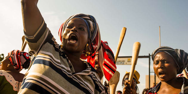 In this photo taken on Monday, Oct. 27, 2014, Woman protest with others during a rally against the longtime president that seeks another term in Ouagadougou, Burkina Faso.  Police used tear gas on Tuesday to disperse an opposition protest in Burkina Faso's capital, as tensions increase ahead of a vote this week on whether the country's longtime president can seek another term. (AP Photo/Theo Renaut)