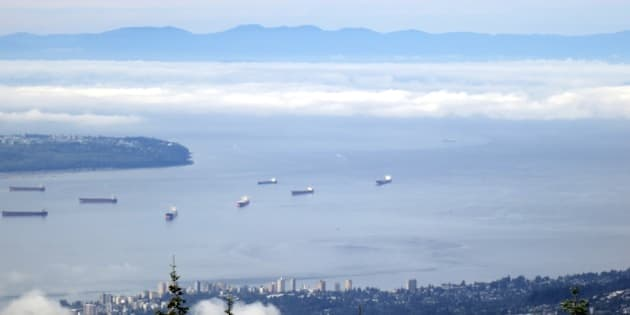 View from Grouse Mountain, showing North Vancouver in the foreground, then freighters moored in English Bay; the tip of UBC peninsula; low cloud over the Strait of Georgia; and the mountains of Vancouver Island in the background.