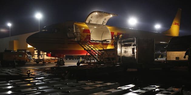 A cargo plane is unloaded on the tarmac during the overnight sort at the DHL Worldwide Express hub of Cincinnati/Northern Kentucky International Airport in Hebron, Kentucky, U.S., on Friday, August 1, 2014. Three of the biggest delivery companies, including DHL Worldwide Express, have released environmental data that show their overall emissions of global warming gases are declining slightly. Photographer: Luke Sharrett/Bloomberg via Getty Images