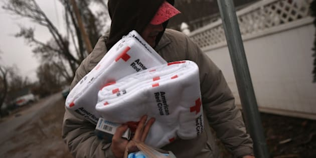 NEW YORK, NY - NOVEMBER 07: Manny Puzzoo carries blankets and other supplies he received from a Red Cross truck near his flood-damaged home on November 7, 2012 in the Staten Island borough of New York City. He and fellow residents of the seaside Midland Beach area of Staten Island braced for a Nor'Easter storm that could potentially re-flood areas devastated by Superstorm Sandy. (Photo by John Moore/Getty Images)