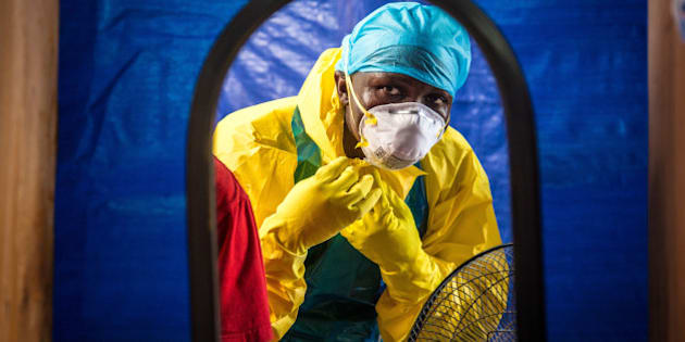 A healthcare worker dons protective gear before entering into an Ebola treatment centre in the west of  Freetown, Sierra Leone, Thursday, Oct. 16, 2014. The deadly Ebola virus has infected two people in what was the last untouched district in Sierra Leone, the government said Thursday, a setback in efforts to stop the spread of the disease in one of the hardest-hit countries. (AP Photo/Michael Duff)