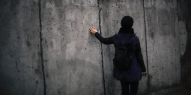 In this photo Oct. 26, 2014 photo a woman touches the wall as she walks alongside the remains of the Berlin Wall at the remembrance site Bernauer Strasse in Berlin. On Nov. 9, 2014, Germany celebrate the 25th anniversary of the fall of the wall on Nov. 9, 1989. After 25 years only a few remains of the wall remind of the about 160 kilometers (about 100 miles) long border which surrounded the west part of Berlin. At the remembrance site Bernauer Strasse some hundred meters of original wall parts still exist. (AP Photo/Markus Schreiber)