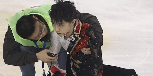 Medical personnel tend to Japanese skater Yuzuru Hanyu (R) on the ice rink after he crashed into Yan Han of China during a practice session before their men's free skating event of the Cup of China ISU Grand Prix of Figure Skating in Shanghai on November 8, 2014.  AFP PHOTO  CHINA OUT        (Photo credit should read STR/AFP/Getty Images)