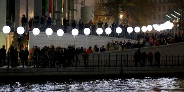 BERLIN, GERMANY - NOVEMBER 09: People gather along the 15 kilometers line enlightened balloons filled with helium gas during the event named 'Lichtgrenze (Light wall)' as part of celebrations for the 25th anniversary of the fall of the Berlin Wall in Berlin, Germany on November 09, 2014. (Photo by Mehmet Kaman/Anadolu Agency/Getty Images)