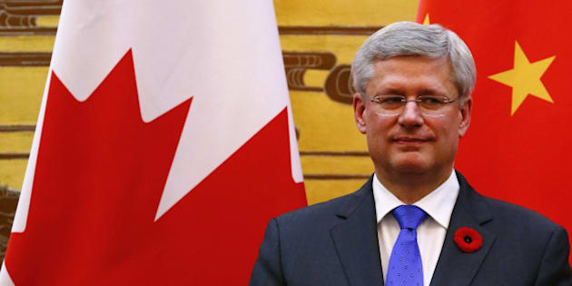 BEIJING, CHINA - NOVEMBER 08: Canada's Prime Minister Stephen Harper stands in front of Chinese and Canadian national flags as he witnesses a signing ceremony with China's Premier Li Keqiang (not pictured) at the Great Hall of the People on November 8, 2014 in Beijing, China. The Canadian prime minister is on a  four-day visit aiming to build closer economic ties with Canadas No. 2 trading partner. (Photo by Petar Kujundzic - Pool/Getty Images)