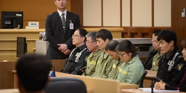 Sewol ferry captain Lee Jun-Seok (3rd R) sits with other crew members inside a a court room in Gwangju at the start of the verdict proceedings on November 11, 2014. After five months of dramatic, often painful testimony, a South Korean court will deliver its verdict -- and possible death sentence -- on the ferry captain at the centre of one of the country's worst peacetime disasters. AFP PHOTO / POOL / Ed Jones        (Photo credit should read ED JONES/AFP/Getty Images)