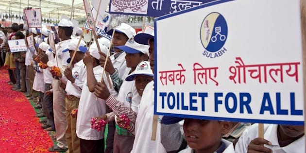 Indian schoolchildren hold placards as they welcome Bindeshwari Pathak, founder and chairman of NGO Sulabh International, at Katra Sahadatgunj village in Badaun on August 31, 2014. More than 100 new toilets were unveiled August 31 in a poverty-stricken and scandal-hit village in northern India, where fearful and vulnerable women have long been forced to defecate in the open. Sanitation charity Sulabh International handed over the brightly coloured structures to cheering villagers in Uttar Pradesh state, just weeks after Prime Minister Narendra Modi announced every household should have a toilet within four years. More than 500 million Indians defecate outdoors, according to the World Bank, particularly in poor, rural areas such as Badaun district in Uttar Pradesh, leaving them exposed to diseases. AFP PHOTO/Prakash SINGH        (Photo credit should read PRAKASH SINGH/AFP/Getty Images)