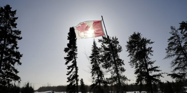A Canadian flag flies over the Berens River in Berens River, Manitoba, Canada, on Thursday, Feb. 14, 2013. About 1.3 million Canadian aboriginals, the youngest and fastest-growing segment of Canada's population, are struggling to reverse centuries of oppression and modern-day neglect. Photographer: Marc Rochette/Bloomberg via Getty Images