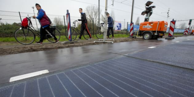 """Bicyclists are forced to use the sidewalk as they pass a stretch of bicycle path where a solar panel roadway is being constructed in Krommenie, north of Amsterdam, Netherlands, Tuesday, Nov. 11, 2014. A project dubbed """"SolaRoad"""" gets underway in the Netherlands this week, testing roadways as a potential canvas to collect solar energy. Fittingly for the cycle-crazy Dutch, the first SolaRoad is a bike path not far from Amsterdam. The path is built of large modules of solar panels, each with heavy-duty glass protecting them from wear. An additional rough translucent plastic coating on top ensures bikers don't slip. (AP Photo/Peter Dejong)"""