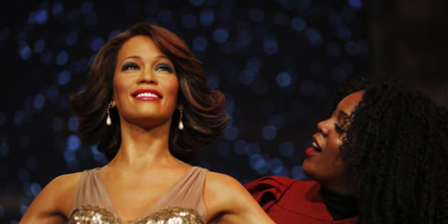 A member of a gospel choir pretends she poses for a picture of herself with the wax figure of late U.S. singer Whitney Houston, as she poses for the photographers at Madame Tussauds in London, Monday, Oct. 21, 2013. (AP Photo/Lefteris Pitarakis)