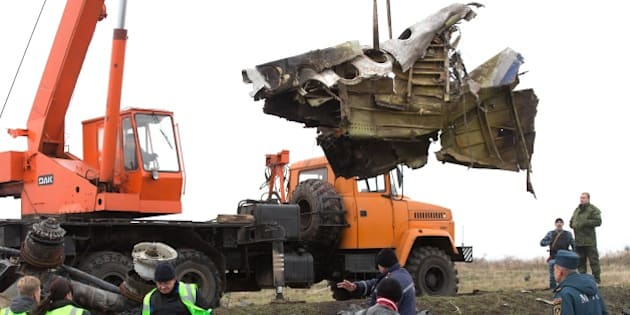 Ministry team workers of the emergency situation of the self-declared Donetsk People's Republic and members of the Dutch expert team collect parts of the Malaysia Airlines Flight MH17 at the crash site near the village of Grabove, in eastern Ukraine as they load them on a truck, on November 16, 2014. Work began to remove the wreckage of Malaysia Airlines flight MH17 from rebel-held territory in eastern Ukraine, four months after it was shot down claiming 298 lives. AFP PHOTO / MENAHEM KAHANA        (Photo credit should read MENAHEM KAHANA/AFP/Getty Images)