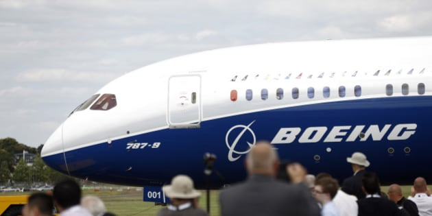 Visitors watch as a Boeing 787-9 Dreamliner aircraft, produced by Boeing Co., taxis on the runway before performing in an aerial flying display on the first day of the Farnborough International Airshow in Farnborough, U.K., on Monday, July 14, 2014. The Farnborough International Air Show, which runs July 14-20, is this year's biggest forum for aircraft introductions and sales. Photographer: Simon Dawson/Bloomberg via Getty Images
