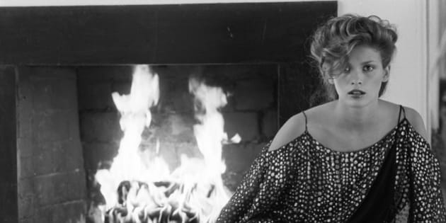 Full-length portrait of American fashion model Gia Carangi (1960 - 1986) as she sits in front of a lit fireplace, dressed in a semi-transparent short with metallic coloured dots, a thin wrap-around belt, and a short skirt, late 1970s to mid 1980s. (Photo by Andrea Blanch/Getty Images)