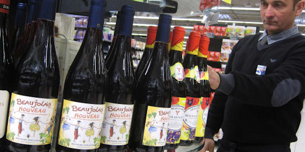 A shop assistant at a store in Nice, southeastern France, arranges bottles of 2013 Beaujolais Nouveau, Thursday, Nov. 21, 2013. According to French law, the wine is released on the third Thursday of each November and this year's theme celebrates the spirit of the roaring 1920's. Beaujolais Nouveau is easy to drink, but everything a fine wine is not: young, poor in tannins and not suited to storage. It's partially because new wines could never hope to stir the imagination the way that the great wines of Bordeaux or Champagne do that the makers of Beaujolais Nouveau resorted to what has become a hugely successful marketing campaign. (AP Photo/Lionel Cironneau)