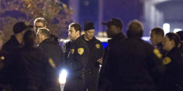 Tallahassee police chief Michael Deleo, center, talks with his officers as they investigate a shooting outside the Strozier library on the Florida State University campus in Tallahassee, Fla. Nov 20, 2014.   The gunman was shot and killed by police officers according to Tallahassee Police spokesman Dave Northway. (AP Photo/Mark Wallheiser)
