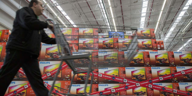 A man pushes a shopping cart past Koninklijke Philips NV televisions that are reserved for the 'El Buen Fin' weekend at a Wal-Mart de Mexico SAB Sam's Club store in Mexico City, Mexico, on Wednesday, Nov. 12, 2014. El Buen Fin, Mexico's equivalent of Black Friday, when the year's biggest discounts are offered by participating stores, is held during the third weekend of November. Photographer: Susana Gonzalez/Bloomberg via Getty Images
