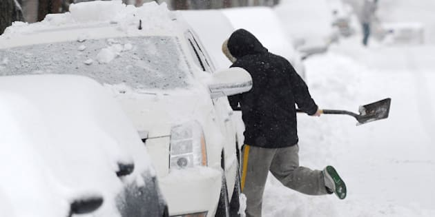 ALEXANDRIA, VA - FEBRUARY 13:  Rustin Pierce shovels snow along Queen St. as a snow storm blows through the region on Thursday February 13, 2014 in Alexandria, VA.  (Photo by Matt McClain/ The Washington Post via Getty Images)