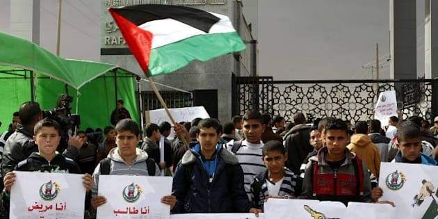 RAFAH, GAZA - NOVEMBER 23: A group of Palestinian students hold banners as they stage demonstration against Egyptian Government to show their demand to re-open border crossing in Rafah, Gaza on November 23, 2014. (Photo by Abed Rahim Khatib/Anadolu Agency/Getty Images)
