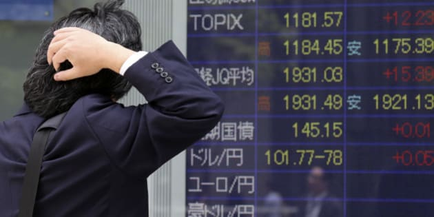 A man looks at an electronic stock board of a securities firm in Tokyo, Friday, May 23, 2014. Japan's Nikkei 225 was up 0.9 percent at 14,473.19 after the dollar climbed to near 102 yen overnight. A weaker yen is a plus for Japan's powerhouse export manufacturers. (AP Photo/Koji Sasahara)