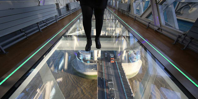 LONDON, ENGLAND - NOVEMBER 10:  A visitor crosses Tower Bridge's new glass walkway on November 10, 2014 in London, England. Unveiled today the glass floor panels along the bridge's high-level walkways weigh 300 kgs each, cost £1m and will give visitors a new view over the historic bridge crossing The River Thames.  (Photo by Peter Macdiarmid/Getty Images)