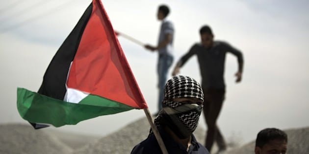 A Palestinian demonstrator holds the national flag during clashes near the border with Israel, east of Gaza City on May 15, 2014, to mark Nakba Day. Palestinians are marking 'Nakba day' which means in Arabic 'catastrophe' in reference to the birth of the state of Israel 66-years-ago in British-mandate Palestine, which led to the displacement of hundreds of thousands of Palestinians who either fled or were driven out of their homes during the 1948 war over Israel's creation. AFP PHOTO/MOHAMMED ABED        (Photo credit should read MOHAMMED ABED/AFP/Getty Images)