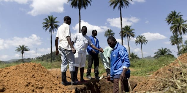 Health workers from Guinea's Red cross wearing Personal Protective Equipments (PPE) prepare to bury bodies of victims of the Ebola virus in Macenta, in Guinea on November 21, 2014.  The deadliest Ebola epidemic on record has killed more than 5,000 people in west Africa and infected almost three times that number, according to the World Health Organization. The virus emerged in Guinea at the start of the year and has infected around 1,900 Guineans, killing almost 1,200. AFP PHOTO KENZO TRIBOUILLARD        (Photo credit should read KENZO TRIBOUILLARD/AFP/Getty Images)