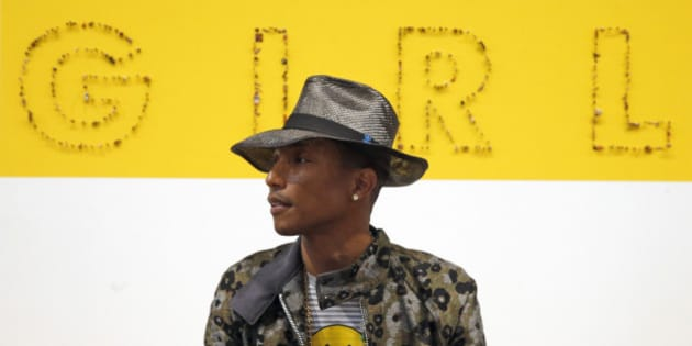 "Singer Pharrell Williams poses during a news conference for the exhibition ""GIRL"" at the Perrotin Gallery in Paris, Monday, May 26, 2014. Williams curated an exhibition encompassing around 40 art pieces, presenting their visions of femininity, muses, female creativity and freedom. The show opens on May 27 and runs through June 27, 2014. The piece behind Williams is ""GIRL"" by French artist Guy Limone. (AP Photo/Francois Mori)"